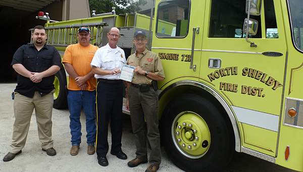 """North Shelby Fire Chief Eugene """"Buddy"""" Tyler hands Kingdom Volunteer Fire Department Chief Tony Miller the title of the reserve engine that North Shelby donated to Kingdom. Also pictured are Kingdom firemen Dale Lucas and Todd Lett. (Contributed)"""