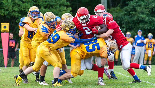 Hope Christian's Zach Gramstad (35) and Jonathan Misso (59) take down a South Haven Christian player on Aug. 16. (Contributed/Twanna Arnold)