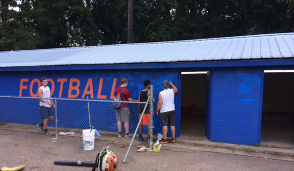 Montevallo High School students add a fresh coat to a building at Theron-Fischer stadium. (Contributed)