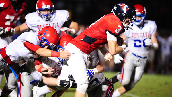 Oak Mountain quarterback Warren Shader drags defenders while reaching for extra yards in a 14-17 overtime win over Vestavia Hills on Sept. 5. (Reporter Photo/Jon Goering)