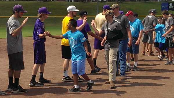 Members of the University of Montevallo baseball team congratulate players in the Calera Field of Angels league. (Contributed)