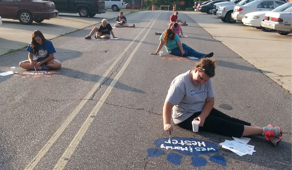 Members of the auxiliary team for the Montevallo Marching Troubadours paint paw prints on Island Street in Montevallo. (Contributed)