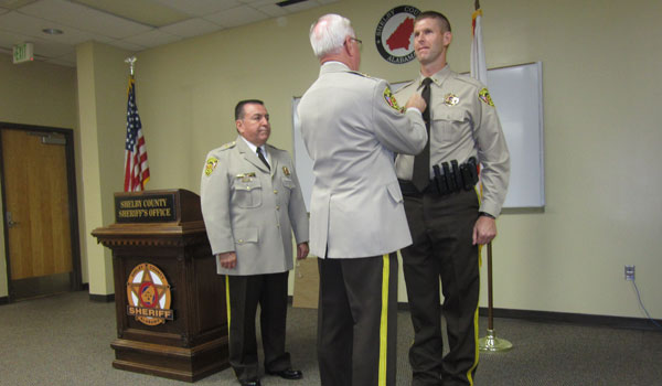 Sheriff Chris Curry honors Lt. Kevin Turner with the award of Meritorious Service.(Ginny Cooper McCarley / Reporter Photo)