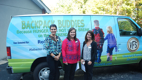From left, members of the Junior League of Birmingham Allison Lassiter, Whitney Saunders and Jessica Naftel pose in front of the Backpack Buddies van. (Reporter Photo/Graham Brooks