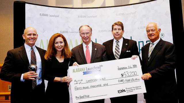 Gary and Mary Martha Parisher, left, with Gov. Robert Bentley, center, who presented them with a check for $43,250 for Cheeriodicals' performance in Alabama Launchpad.