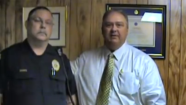 Alabaster Police Chief Curtis Rigney, right, showcases officer David Sharp's mustache, left, in an Oct. 29 video posted to the department's Facebook page. (Contributed)