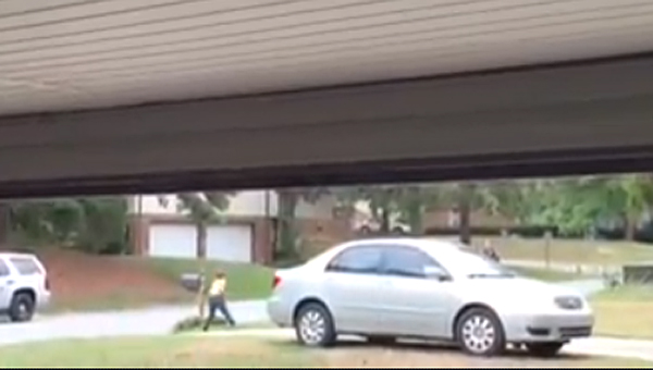 A still shot from a video captured by a neighbor depicts Lt. Jason Boyd, right, tossing a football with a young boy. (Contributed)