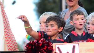 An Alabaster youth football player tosses candy from a float during the parade. (Reporter Photo/Neal Wagner)