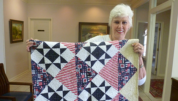 """Sarah Atchison is holding the """"in honor of"""" quilt she made for the grand door prize at the Columbiana Quilt Walk to be given away to those who have collected 10 different quilt patterns of the 25 quilt stops at the Columbiana Quilt Walk on Oct. 11. (Contributed)"""