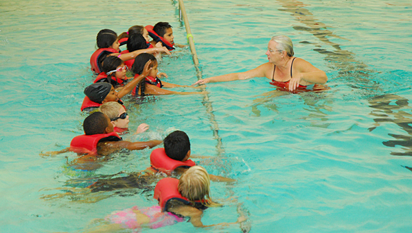 Alabaster YMCA lifeguard Deb Jones, right, teaches a group of Meadow View Elementary School second-graders to swim at the YMCA on Oct. 29. (Reporter Photo/Neal Wagner)