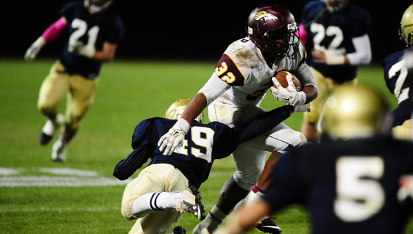 Briarwood's James Holliday attempts to bring down Madison Academy's Malik Miller in an Oct. 31 contest. (Reporter Photo/Jon Goering)