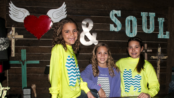 Happy Heart & Soul customers sporting new Husky-themed T-shirts are sisters Peyton, Julia and Grace Wilkins.