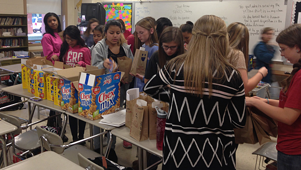 Students in Thompson Middle School's National Junior Honor Society pack bags after school to deliver to patients at the Shelby Comprehensive Cancer Center. (Contributed)