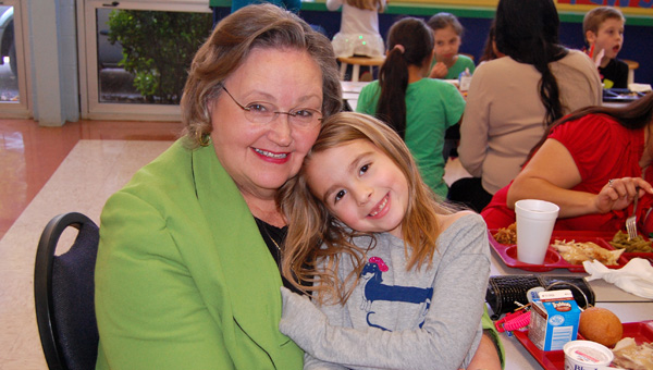 Second grader Juliet Carden hugs her grandmother Margaret Johnson at Valley Elementary School's Thanksgiving lunch on Nov. 21. (Reporter Photo / Molly Davidson)