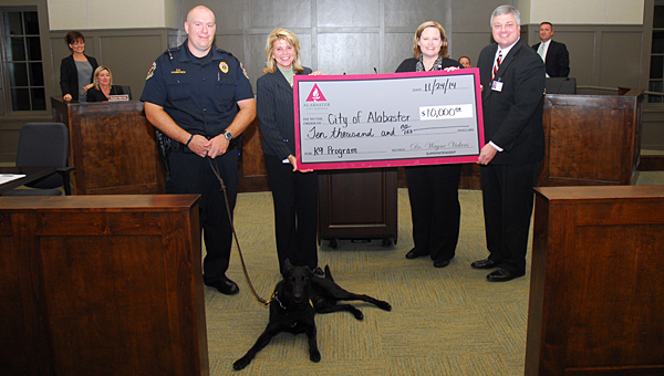 Alabaster School Superintendent Dr. Wayne Vickers, right, and ACS Student Services Coordinator Dorann Tanner, second from right, present a donation to, from left, Alabaster police officer Hunter Hammonds, Alabaster Mayor Marty Handlon and Micco the K-9 officer during a Nov. 24 City Council meeting. (Reporter Photo/Neal Wagner)