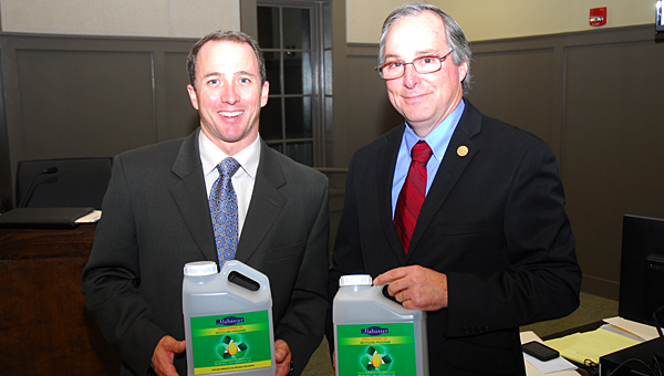 Alabaster City Council members, from left, Russell Bedsole and Rick Walters display jugs to be distributed to residents through Alabaster's new grease recycling program. (Reporter Photo/Neal Wagner)