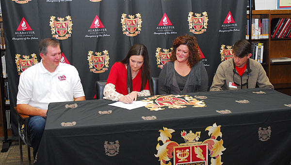 Thompson High School senior Taylin McCarver, second from left, signs a scholarship with the University of West Alabama while flanked by family members during a Nov. 14 ceremony at THS. (Reporter Photo/Neal Wagner)