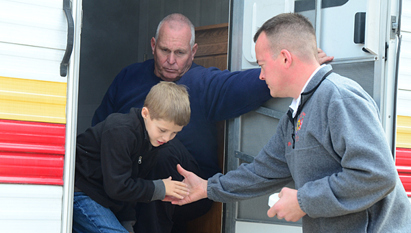 """Alabaster Fire Marshal Capt. Skip Leslie, left, and Lt. Chip Brantley, right, help Meadow View Elementary School second-grader Drew Toth out of the """"smokehouse"""" simulator at the school on Nov. 25. (Reporter Photo/Neal Wagner)"""