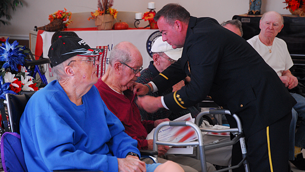 Pelham Fire Department Lt. Ricky King, an Air Force veteran, pins fellow veteran Jewel Gable during a Nov. 14 Veterans Day ceremony at Shelby Ridge in Alabaster. (Reporter Photo/Neal Wagner)