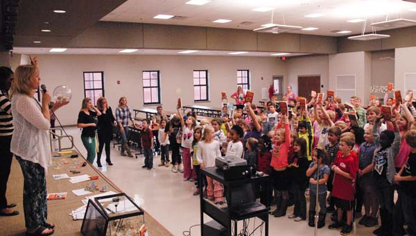 """Students in the Forest Oaks Book Club hold up their copies of """"The World According to Humphrey"""" during a celebration Dec. 4. Also pictured (far left) is library media specialist Jill Haglund holds the school's pet hamster, Mrs. Humphrey. (Reporter photo/Emily Sparacino)"""