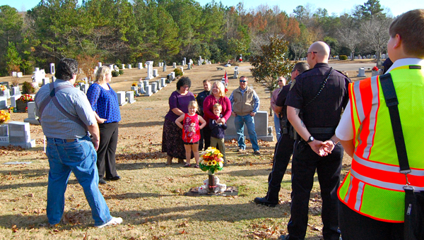 Pelham police officer Philip Davis's widow, Paula Davis, and his two children stand in front of his grave, surrounded by friends, family and fellow police officers, during a Dec. 7 memorial service at Southern Heritage Cemetery. (Reporter Photo / Molly Davidson)