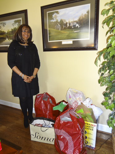 Greystone Ladies Club President Mechelle Wilder stands next to the items that members brought for Hannah Home, a charity the club supports. (Reporter Photo/Emily Sparacino)