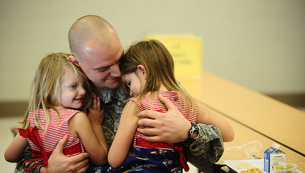Staff Sgt. Michael Daugherty is reunited with his daughters Gracie and Sophie Daugherty at Chelsea Park Elementary School on Friday, Dec. 12. Michael is home from his deployment in Japan where he has been since August. (Reporter Photo/Jon Goering)