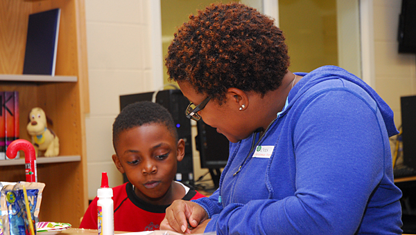 """Big Brothers Big Sisters mentor Rani Crear works with her """"Little Brother,"""" Keelan Howard, during a ceremony in the Creek View Elementary School library on Dec. 15. (Reporter Photo/Neal Wagner)"""