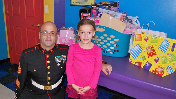 Marine Corps Reserve Toys for Tots Coordinator Sgt. Curtis Wentworth with Allyson Pieper. Allyson Pieper donated all of her presents from her Dec. 6 birthday party to Toys for Tots. (Reporter Photo / Molly Davidson)