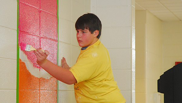 Thompson Middle School student Will Vickers joins his classmates in painting a mural at the Warrior Center for special-needs students on Dec. 3. (Reporter Photo/Neal Wagner)