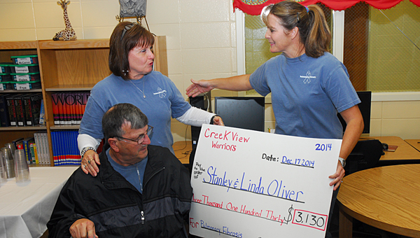 Creek View Elementary School physical education teacher Catherine Mohon, right, presents a donation to CVES secretary Linda Oliver and her husband, former Alabaster police chief Stanley Oliver. (Reporter Photo/Neal Wagner)