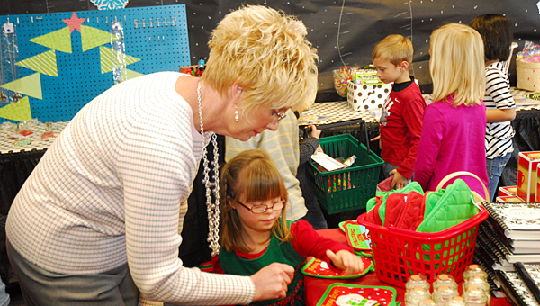 Meadow View Elementary School special education aide Paula Harper, left, helps MVES kindergartener Allie Lovell select presents at the school's Santa shop. (Reporter Photo/Neal Wagner)