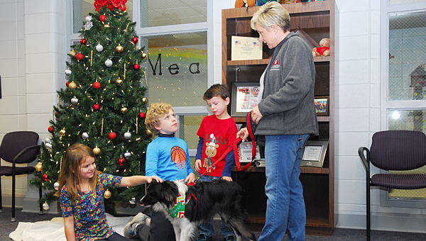 Meadow View Elementary School students, from left, Aubree Dotson, Alex Galloway and Morgan Carden greet Warrior the dog and his handler, Windy McNish, at the school on Dec. 12. (Reporter Photo/Neal Wagner)