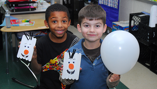 "Warrior Center students Jordan Lacey and Preston Strickland show off their creations during the school's ""Frozen"" themed Christmas party on Dec. 18. (Reporter Photo/Neal Wagner)"