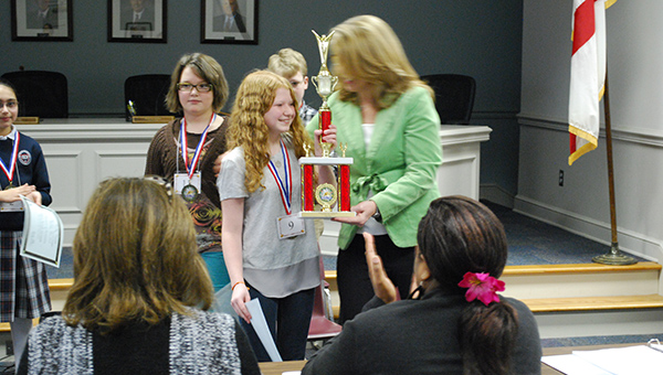 Thompson Middle School seventh-grader Abby Malkove receives the first place trophy after winning the Shelby County Spelling Bee on Friday, Jan. 23 (Reporter Photo/Graham Brooks)