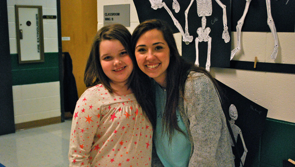 OMES third grader Lizzie Sewell with Anna English, an Eagle Advisor and OMHS senior, during a visit from the Eagle Advisors on Jan. 22. (Reporter Photo / Molly Davidson)