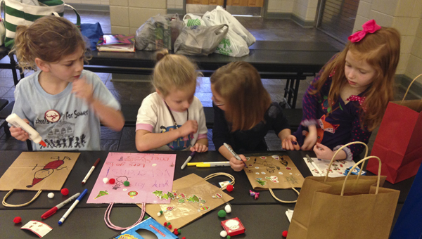Daisy Girl Scout Troop No. 600 members Kate Martin, Wren Whitaker, Isabeau Maxwell and Brianna Emerson decorate gift bags for local veterans through the Three Hots and a Cot program. (Contributed)