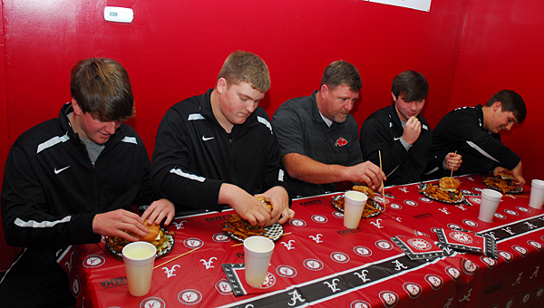 Thompson High School Principal Chris Tangle, center, joins THS football players in testing out the Bama burger at Chubb's Grub Station on Dec. 31. (Reporter Photo/Neal Wagner)