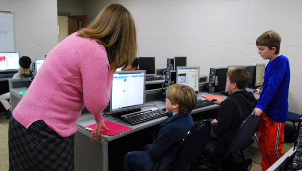 Forest Oaks teacher Adrienne McKinney guides a student during a Jan. 23 meeting of the Forest Oaks Elementary School coding club. (Reporter Photo / Molly Davidson)