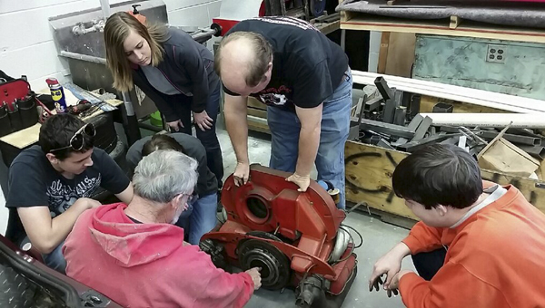 A group of Thompson High School students, their teacher, Brian Copes, and retired master electrician Miles Jackson, are working to convert a 1974 Bradley into an electric car. (Photo by Ginny Cooper McCarley/Special to the Reporter)