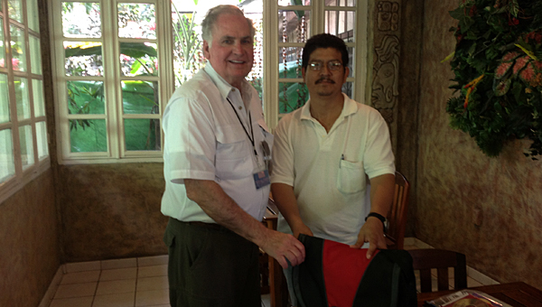 Evangel Presbyterian Church member Carlton LeMond presents a laptop to a pastor in San Ignacio, Belize, to be used for seminary training during a mission trip to the country in 2014. (Contributed)