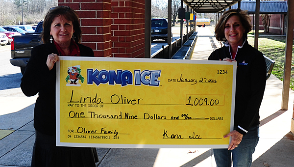 Kona Ice owner Karla Butler, right, presents a $1,009 check to Creek View Elementary School secretary Linda Oliver, left, at the school on Jan. 27. (Reporter Photo/Neal Wagner)