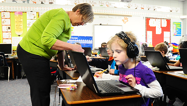 Meadow View Elementary School student Haley Sutton, right, completes a lesson with one of the school's new laptops while MVES teacher Lynda Glass, left, helps another student. (Reporter Photo/Neal Wagner)