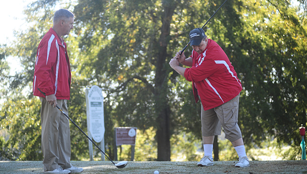 David Litton, left, and Rusty Montgomery, right, practice their golf swings at Montevallo golf course. (Reporter Photo/Jon Goering)
