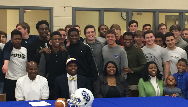 Josh Pugh (seated, middle) with his football and basketball teammates after he signed his letter of intent to play football at Miles College. (Reporter Photo / Baker Ellis)