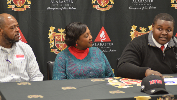 Melvin Owens, with his parents, signed his letter of intent to play football for Mississippi Valley State University on Feb. 9. (Reporter Photo / Baker Ellis)