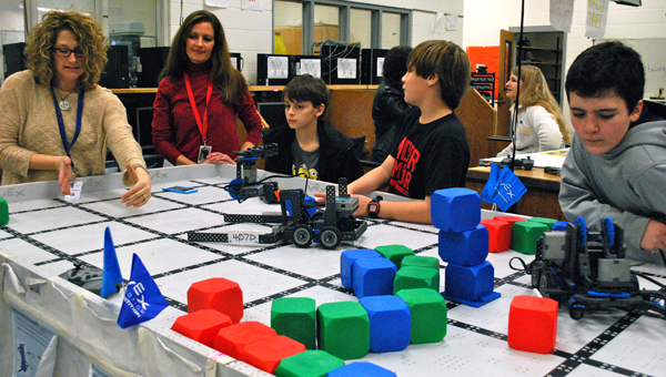 Robotics sponsors Sherri Whitehead, right, and Dana Furman, left, help students talk through ways to improve their robots during a Jan. 30 practice at Oak Mountain Middle School. (Reporter Photo / Molly Davidson)