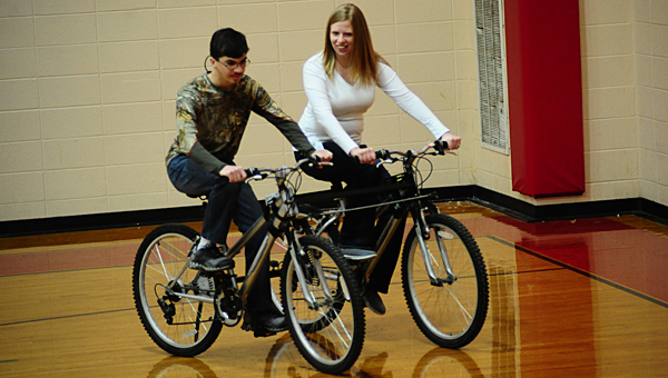Thompson High School special-education student Camron Carter, left, and his teacher, Diana Wagoner, pilot a student-designed tandem bike system around the THS auxiliary gym on Feb. 19. (Reporter Photo/Neal Wagner)