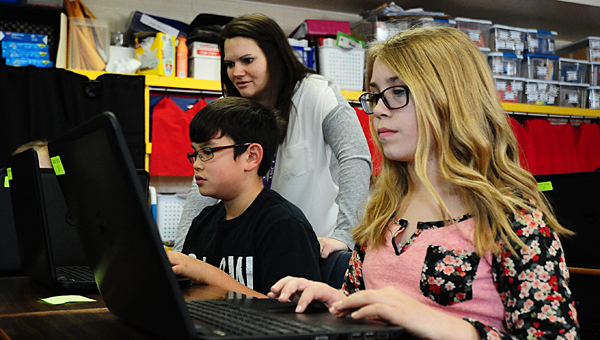 TIS gifted specialist Nicole Naro helps fifth-graders, from left, Cameron Corbitt and Sarah Turner during a coding exercise on Feb. 18. (Reporter Photo/Neal Wagner)