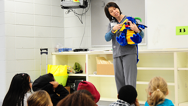 "Kelly Pitts, a dental hygenist with Alabaster Pediatric Dentistry, uses ""Maggie"" the stuffed dragon to demonstrate proper brushing techniques to a group of MVES second-graders on Feb. 4. (Reporter Photo/Neal Wagner)"